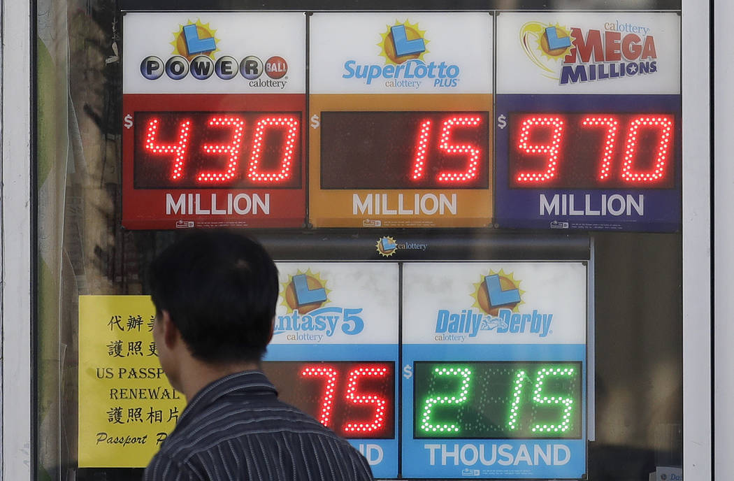 A man walks past Mega Millions and other lottery displays outside of The Lucky Spot in San Francisco, Thursday, Oct. 18, 2018. The Mega Millions jackpot has climbed to $970 million, inching ever-c ...