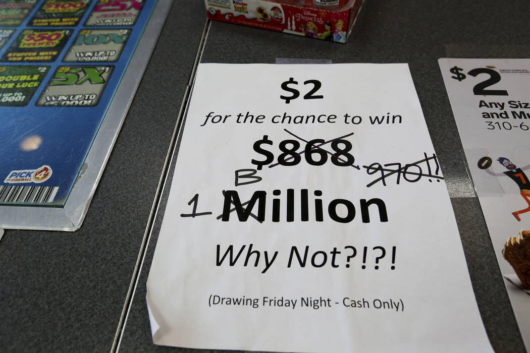 An updated paper sign is displayed the counter of a 7-Eleven store shows that the Mega Millions estimated jackpot has soared to $1 billion, as the second-largest prize in U.S. lottery history gets ...