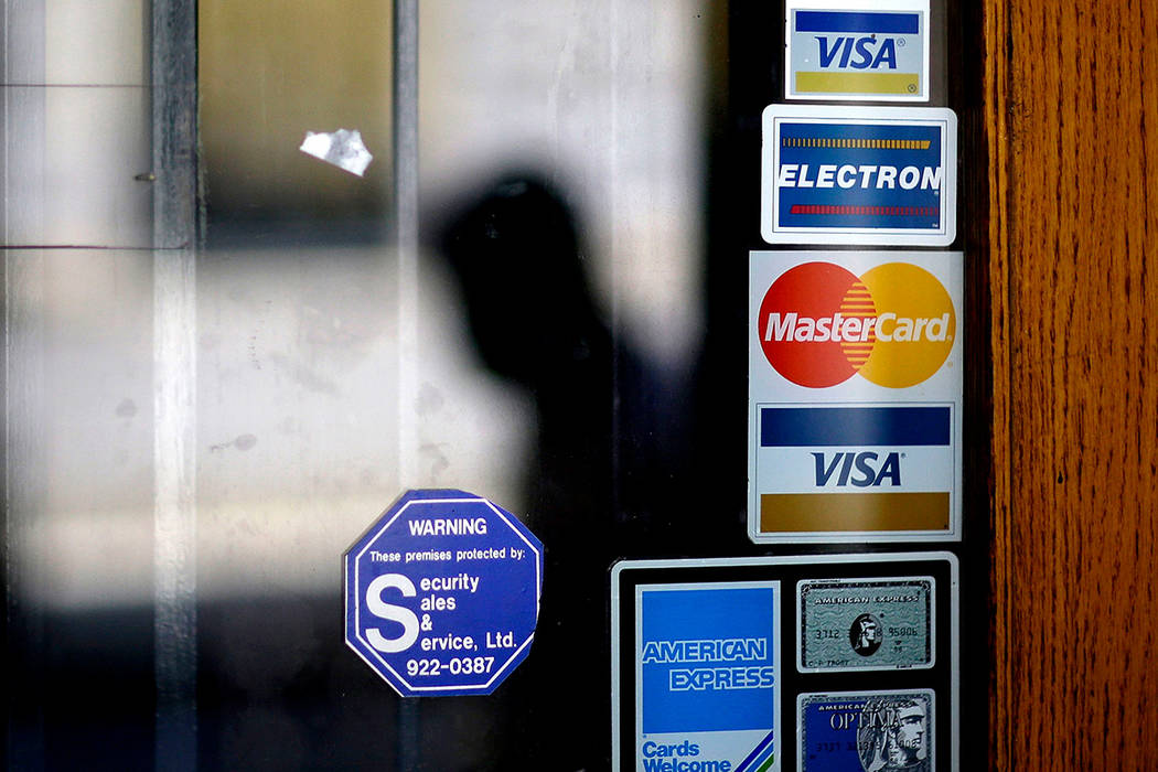 A pedestrian walks past credit card logos posted on a downtown storefront in Atlanta on July 18, 2012. The Federal Deposit Insurance Corporation says the number of Americans who do not have a bank ...