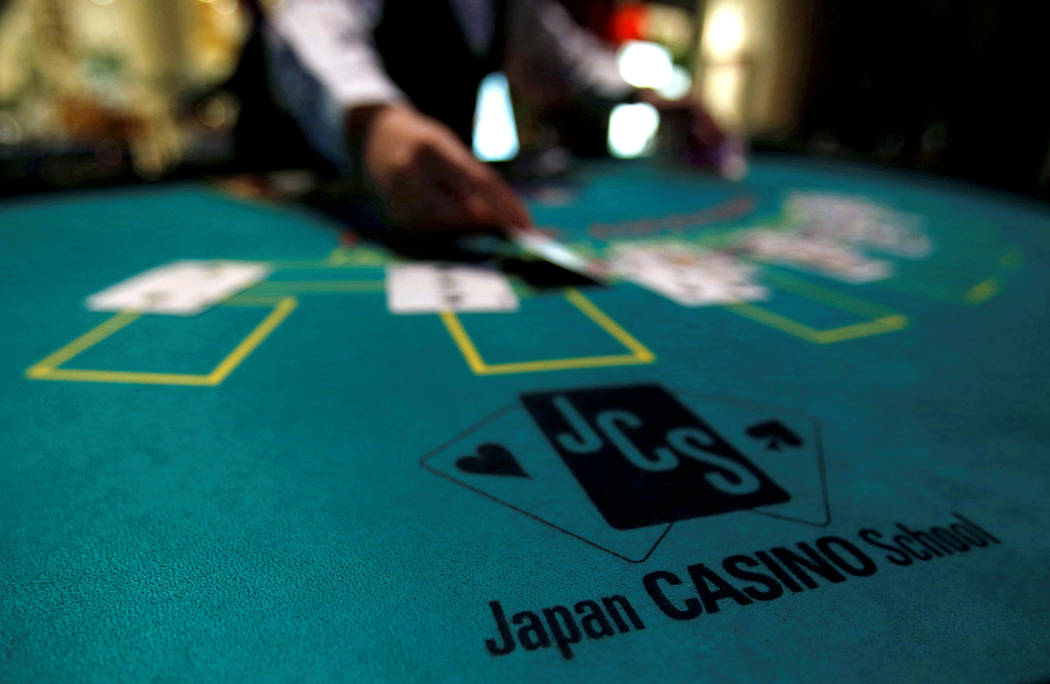 A logo of Japan casino school is seen as a dealer puts cards on a mock black jack casino table during a photo opportunity at an international tourism promotion symposium in Tokyo, Japan September ...