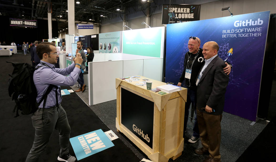 William Baxter takes a photo of colleague Ted Mlynar, right, both of New York, with Christian Lewis of Phoenix at the GitHub booth at the Money 20/20 show at the Venetian in Las Vegas Tuesday, Oct ...