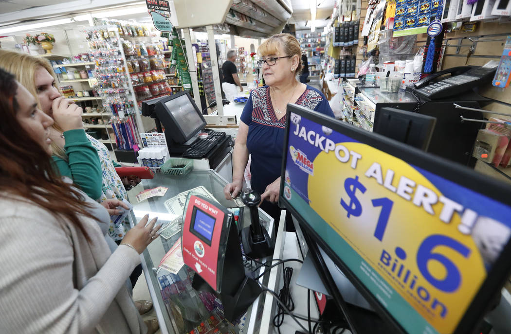Daysi Lorenzo, center, sells lottery tickets, Monday, Oct. 22, 2018, at La Preferida Superdiscount store in Hialeah, Fla. Lottery players will have a chance at winning an estimated $1.6 billion ja ...