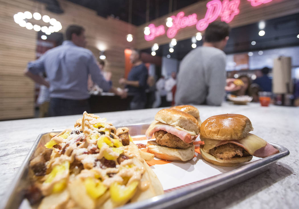 An order of Shaq Daddy sliders and Dirty Fries sits on the bar during the grand opening celebration of Big Chicken, Shaquille O'Neal's new fast-casual chicken restaurant located at 4480 Paradise R ...
