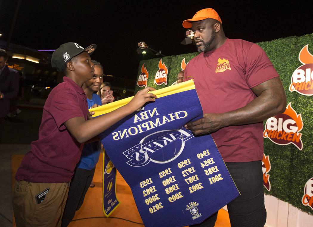 Retired NBA player Shaquille O'Neal signs a Lakers championship banner for 11-year-old Amare Oba during the grand opening celebration of Big Chicken, Shaq's new fast-casual chicken restaurant loca ...
