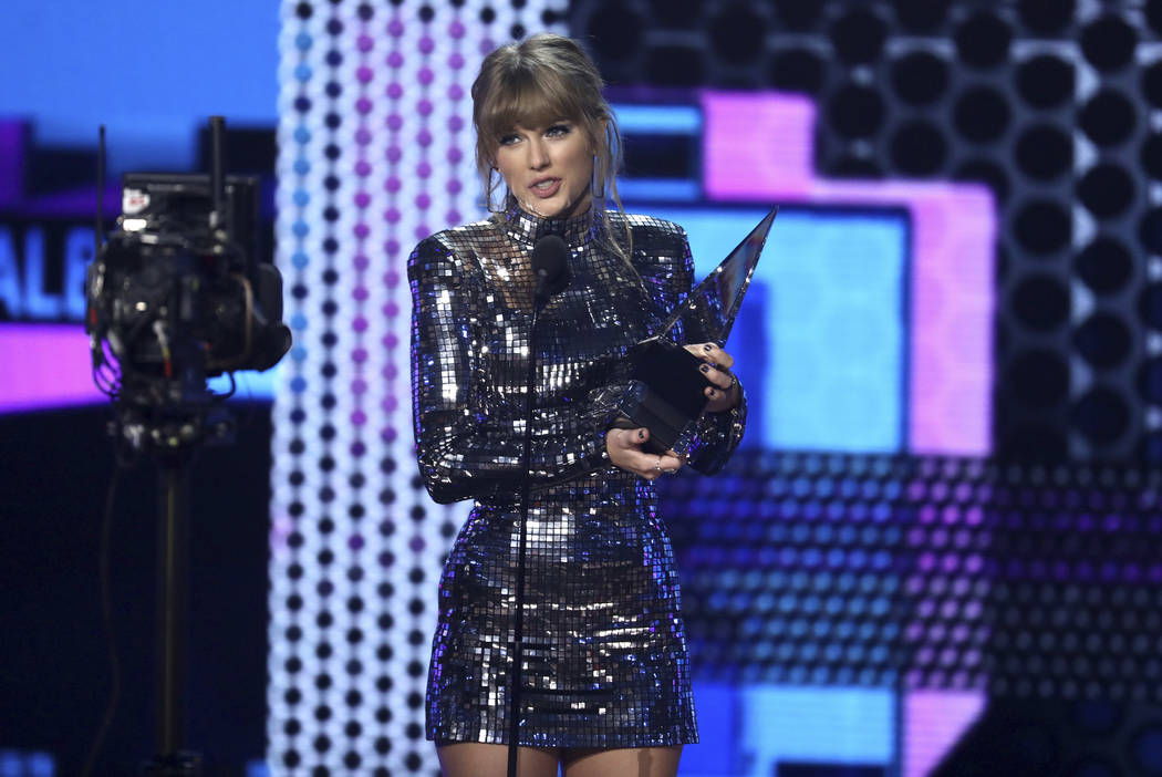 """Taylor Swift accepts the award for favorite pop/rock album for """"Reputation"""" at the American Music Awards on Tuesday, Oct. 9, 2018, at the Microsoft Theater in Los Angeles. (Matt Sayles/Invision/AP)"""