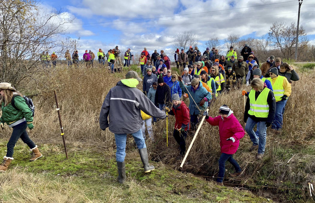 Volunteers cross a creek and barbed wire near Barron, Wis., Tuesday, Oct. 23, 2018, on their way to a ground search for 13-year-old Jayme Closs who was discovered missing Oct. 15 after her parents ...