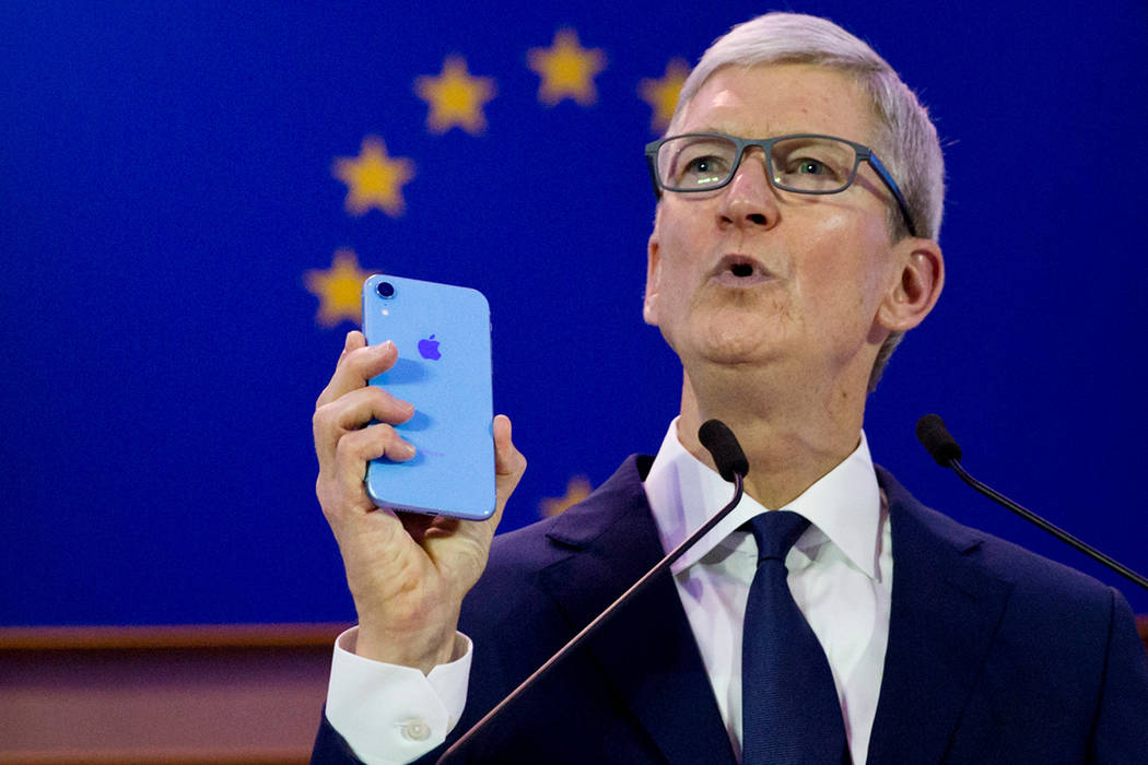 Apple CEO Tim Cook holds up an iPhone as he speaks during a data privacy conference at the European Parliament in Brussels, Wednesday, Oct. 24, 2018. (AP Photo/Virginia Mayo)