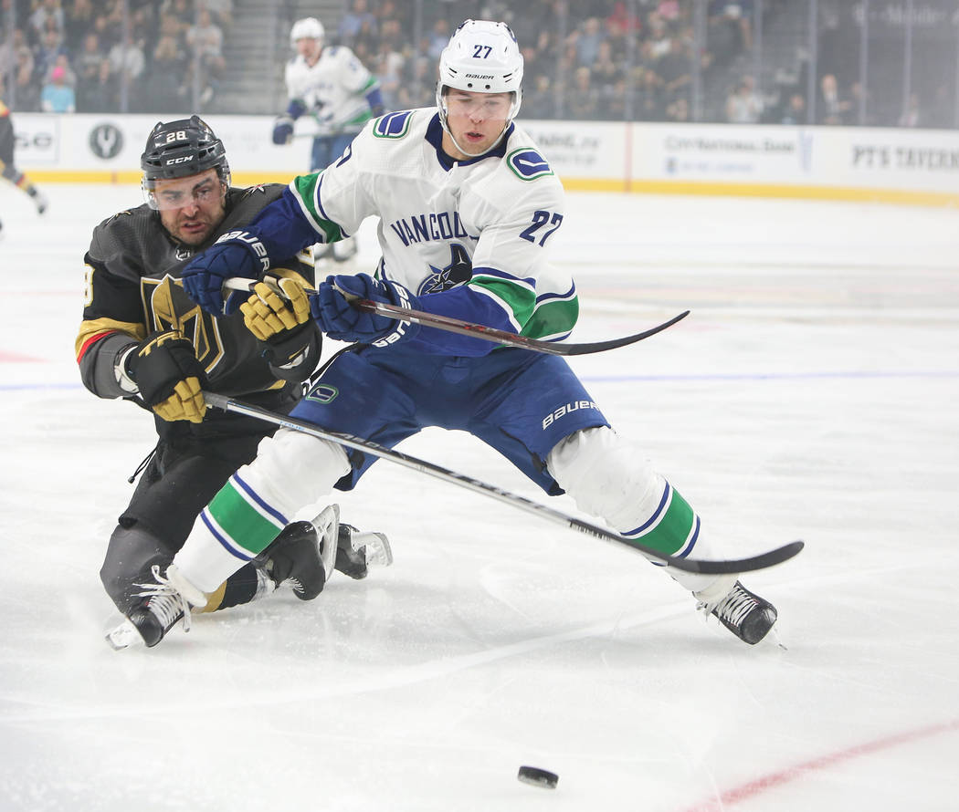 Golden Knights left wing William Carrier (28) gets blocked from the puck by Vancouver Canucks defenseman Ben Hutton (27) during the first period of an NHL hockey game at T-Mobile Arena in Las Vega ...