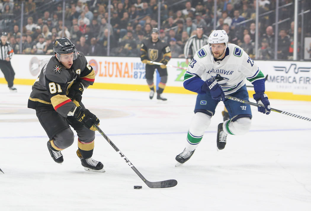 Golden Knights center Jonathan Marchessault (81) skates past Vancouver Canucks defenseman Alexander Edler (23) with the puck during the first period of an NHL hockey game at T-Mobile Arena in Las ...