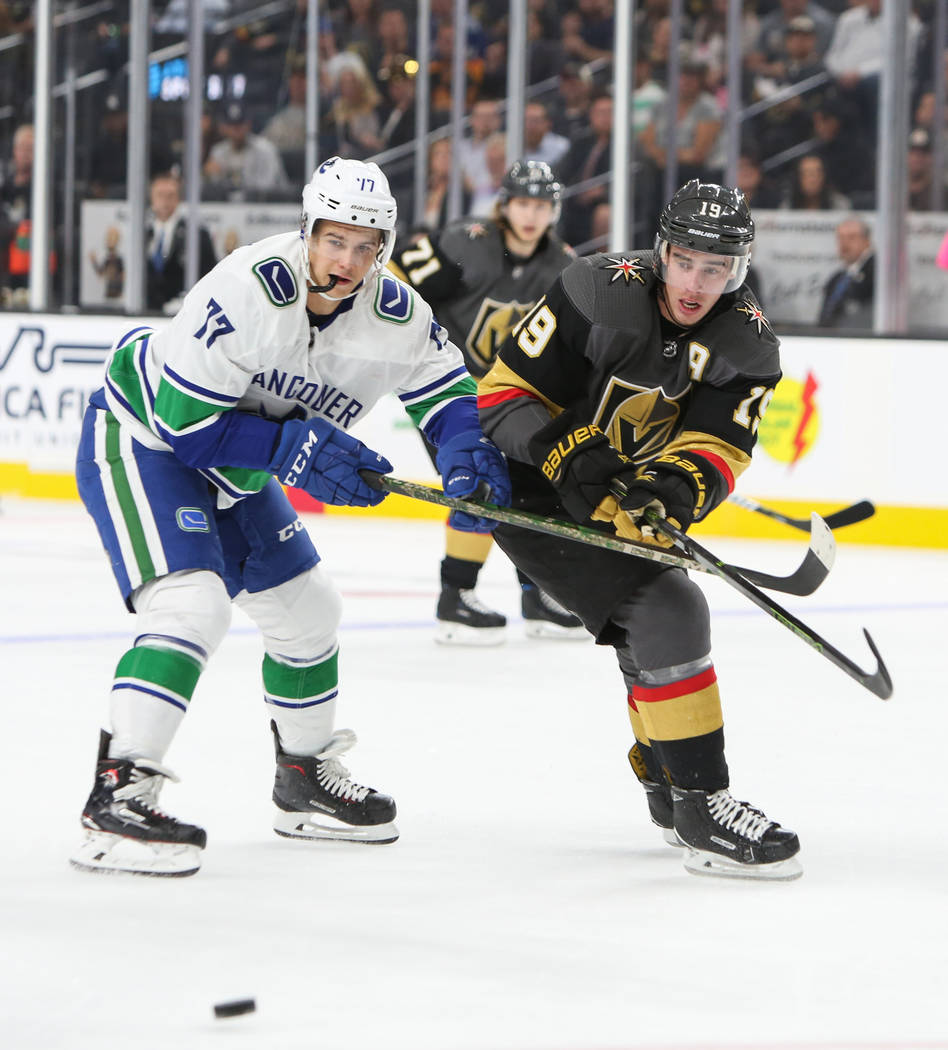 Golden Knights right wing Reilly Smith (19) passes the puck to a teammate while under pressure from Vancouver Canucks right wing Nikolay Goldobin (77) during the first period of an NHL hockey game ...