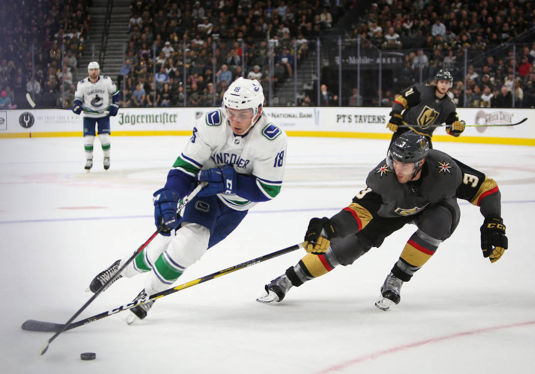 Golden Knights defenseman Brayden McNabb (3) reaches for the puck against Vancouver Canucks right wing Jake Virtanen (18) during the second period of an NHL hockey game at T-Mobile Arena in Las Ve ...
