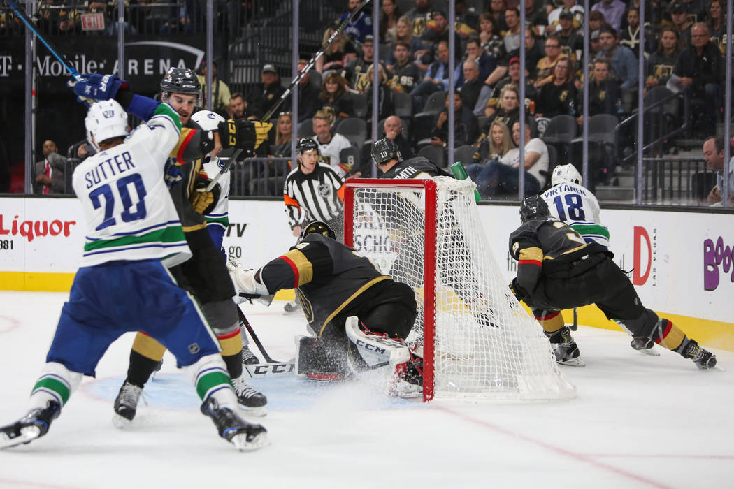 Vancouver Canucks right wing Jake Virtanen (18) takes the puck behind the Golden Knights' goal during the second period of an NHL hockey game at T-Mobile Arena in Las Vegas, Wednesday, Oct. 24, 20 ...