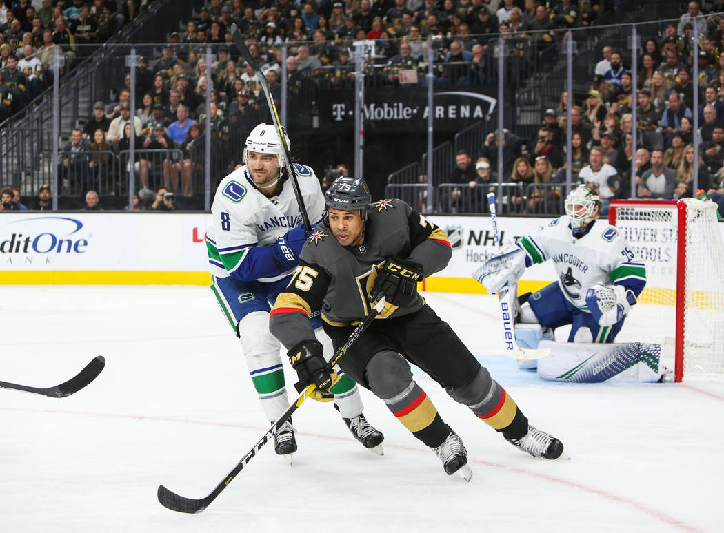 Golden Knights right wing Ryan Reaves (75) passes to a teammate under pressure from Vancouver Canucks defenseman Christopher Tanev (8) during the third period of an NHL hockey game at T-Mobile Are ...