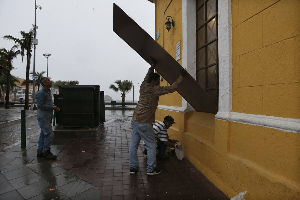 Workers board up windows prior the landfall of Hurricane Willa, in Mazatlan, Mexico, Tuesday, Oct. 23, 2018. Emergency officials said they evacuated more than 4,250 people in coastal towns and set ...