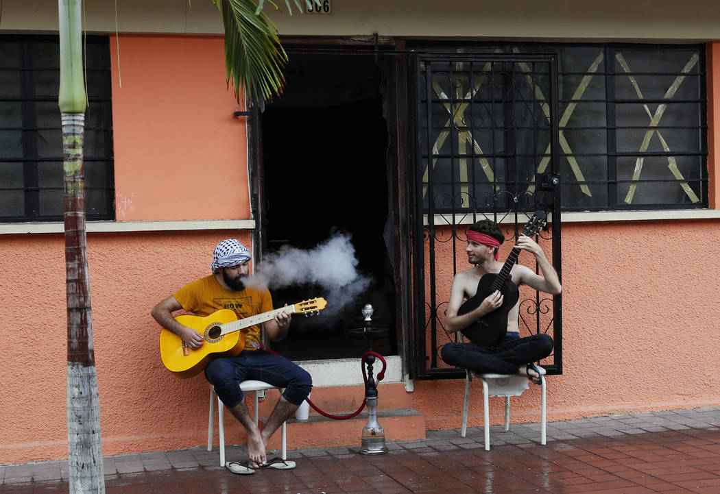 Two young men smoke and play their guitars as they wait for the landfall of Hurricane Willa in Mazatlan, Mexico, Tuesday, Oct. 23, 2018. Emergency officials said they evacuated more than 4,250 peo ...