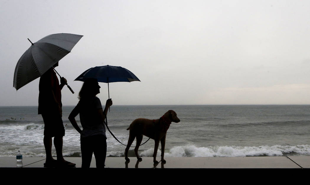 A couple and their dog stand of the seawall prior the landfall of Hurricane Willa, in Mazatlan, Mexico, Tuesday, Oct. 23, 2018. Emergency officials said they evacuated more than 4,250 people in co ...