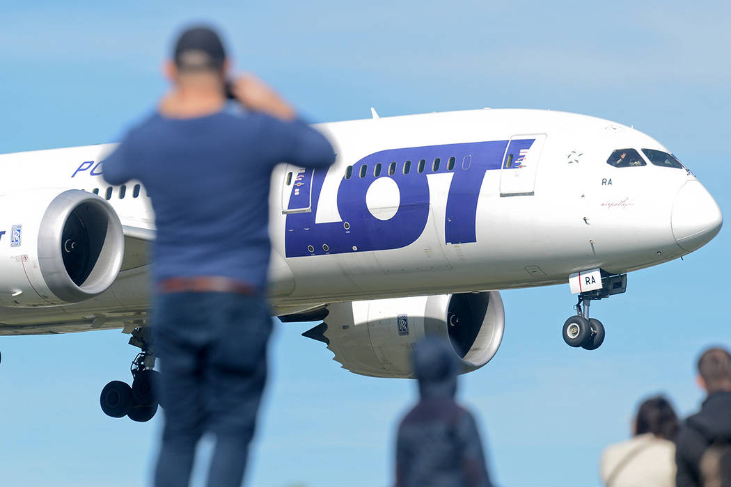 People watch a landing Polish Airlines LOT jetliner at the Chopin airport in Warsaw, Poland. Poland's national airline LOT is cancelling some flights since Oct. 22, 2018, as some crew members don' ...