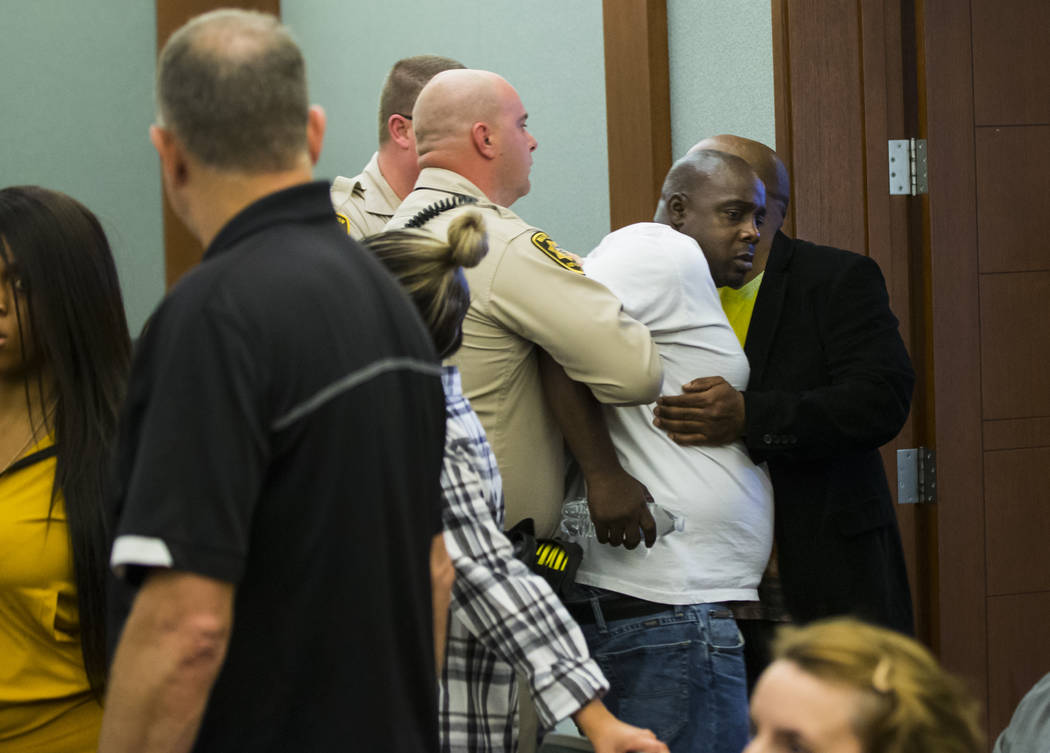 Bailiffs restrain a family member of Tinesha Antovia Adams as jury selection goes on in the trial of Norman Smith, accused of shooting and killing Adams, who was pregnant, at the Regional Justice ...