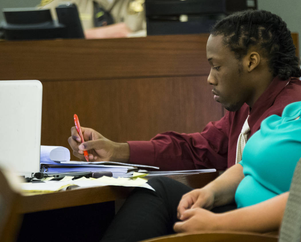 Norman Smith, accused of shooting and killing Tinesha Antovia Adams, who was pregnant, takes notes during jury selection for his trial at the Regional Justice Center in Las Vegas on Tuesday, Oct. ...
