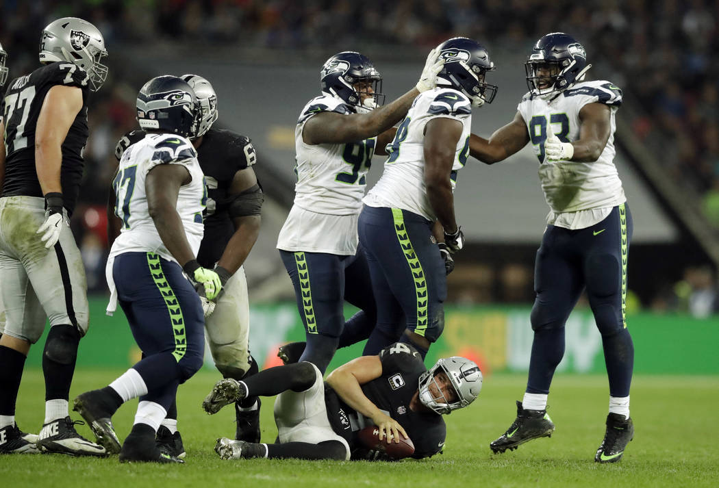 Seattle Seahawks players react after sacking Oakland Raiders quarterback Derek Carr (4), bottom center, during the second half of an NFL football game at Wembley stadium in London, Sunday, Oct. 14 ...