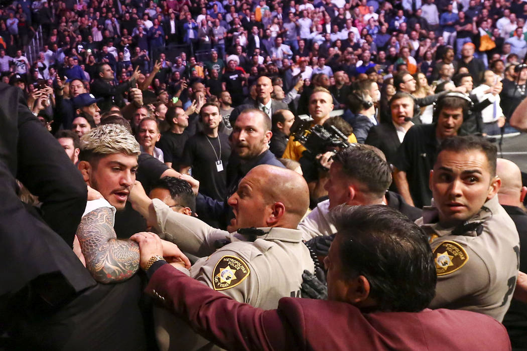 Las Vegas police and security try to stop Dillon Danis, who serves as McGregor's jiu-jitsu coach, left, during fights that broke out after Khabib Nurmagomedov beat Conor McGregor at UFC 229 at T-M ...