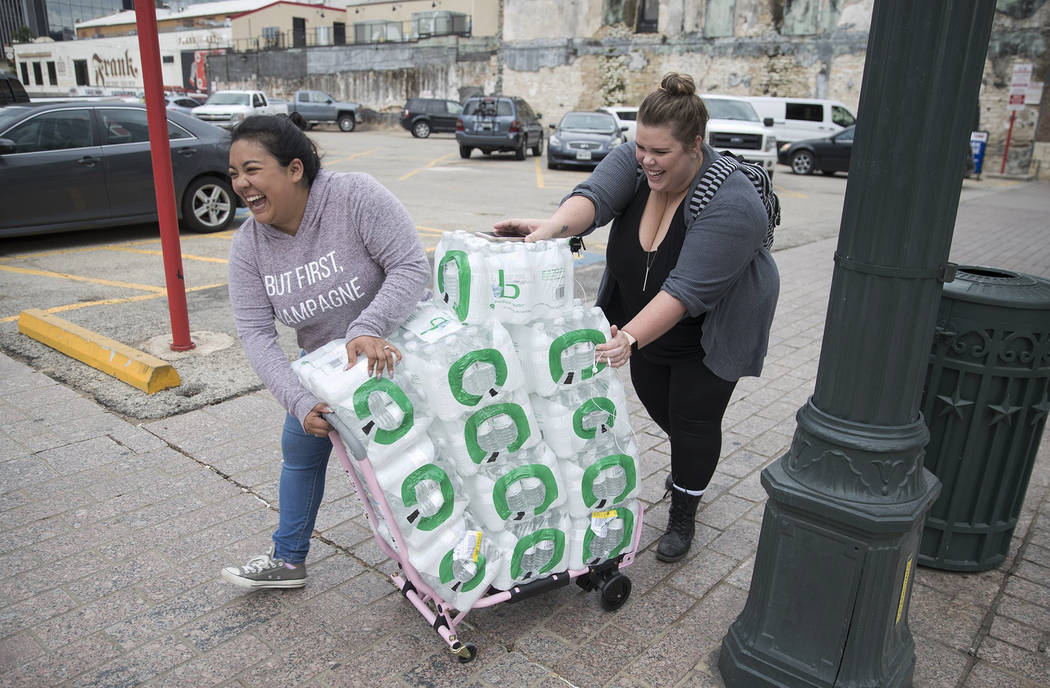 Alyssa Aclcala and Katie Killbourne walk 4 blocks or more from their downtown office Monday, October 22, 2018 after purchasing 12 cases of water from CVS in Austin, Texas The city of Austin's wate ...