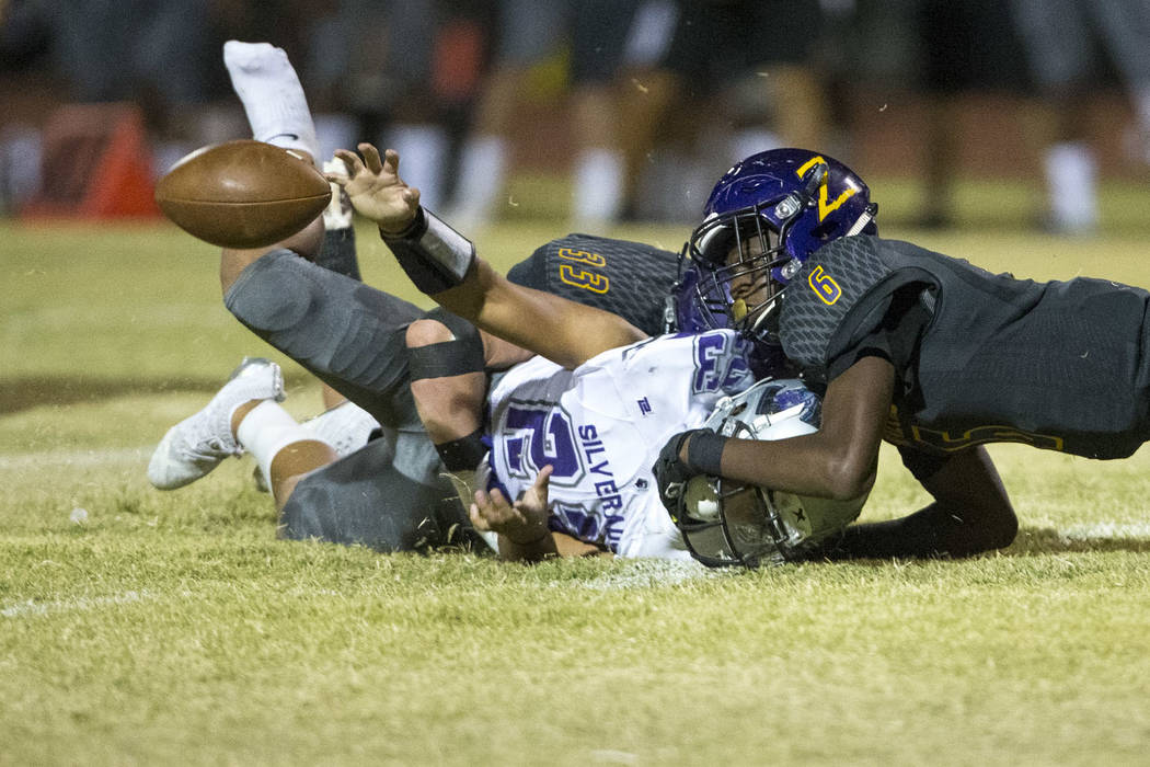 Silverado's Breven Palpallatoc (23), left, fumbles the ball as he is tackled by Durango's Michael Hayword (6)during the first half of a varsity football game at Durango High School in Las Ve ...