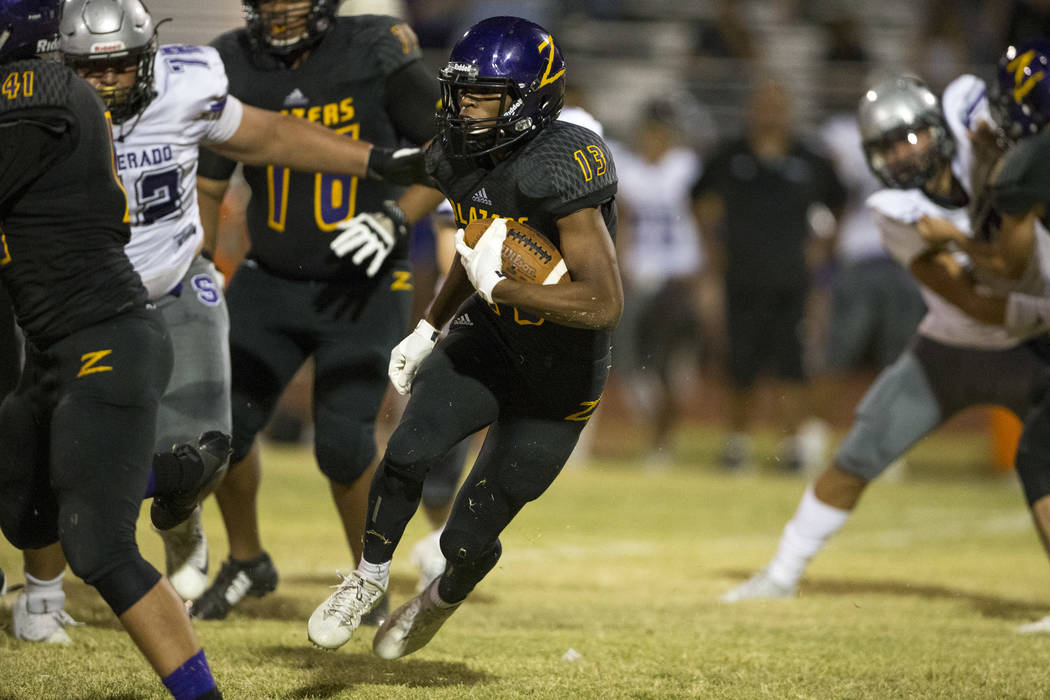 Durango's Justin Johnson (13) runs the ball against Silverado defenders during the first half of a varsity football game at Durango High School in Las Vegas on Friday, Sept. 21, 2018. Richard Bria ...