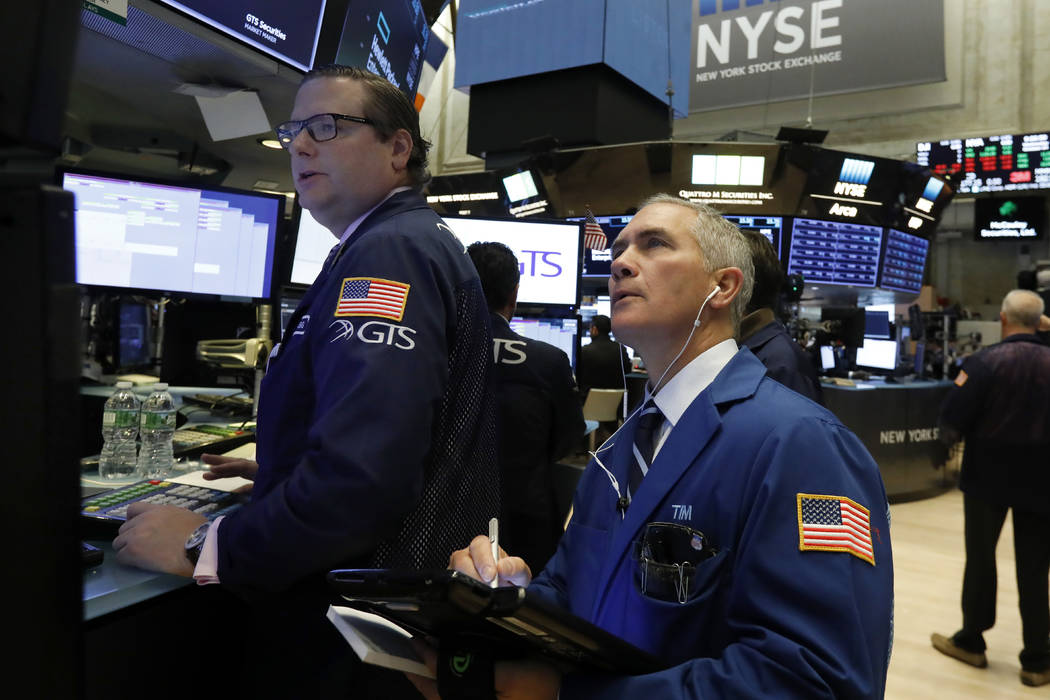 Specialist Gregg Maloney, left, and trader Timothy Nick work on the floor of the New York Stock Exchange, Wednesday, Oct. 24, 2018. Stocks are off to a mixed start on Wall Street as gains for Boei ...