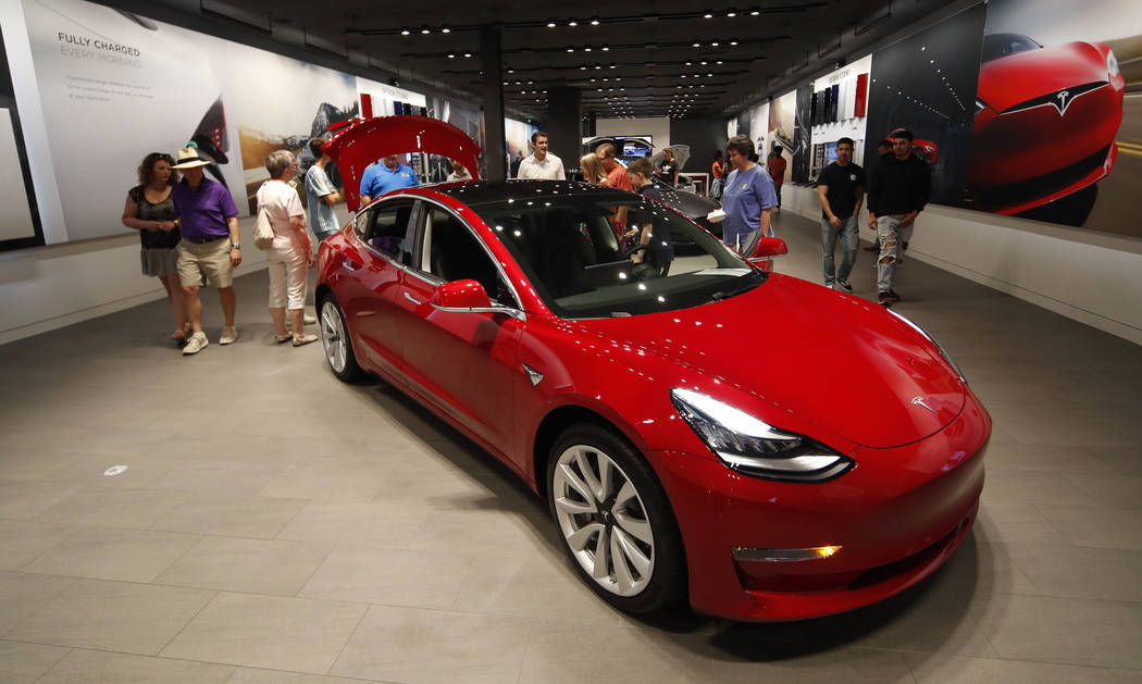 FILE- In this July 6, 2018, file photo prospective customers confer with sales associates as a Model 3 sits on display in a Tesla showroom in the Cherry Creek Mall in Denver. Tesla Inc. reports ea ...