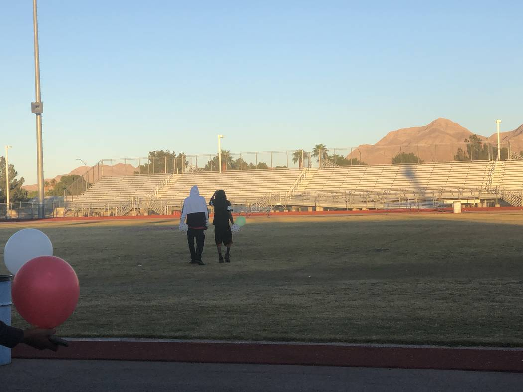 Susan Nash's sons, De'Angelo and De'Andre Nash, right, walk to the center of Desert Pines High School's football field, where a heart with their mother's initials was painted, on Oct. 24, 2018. A ...