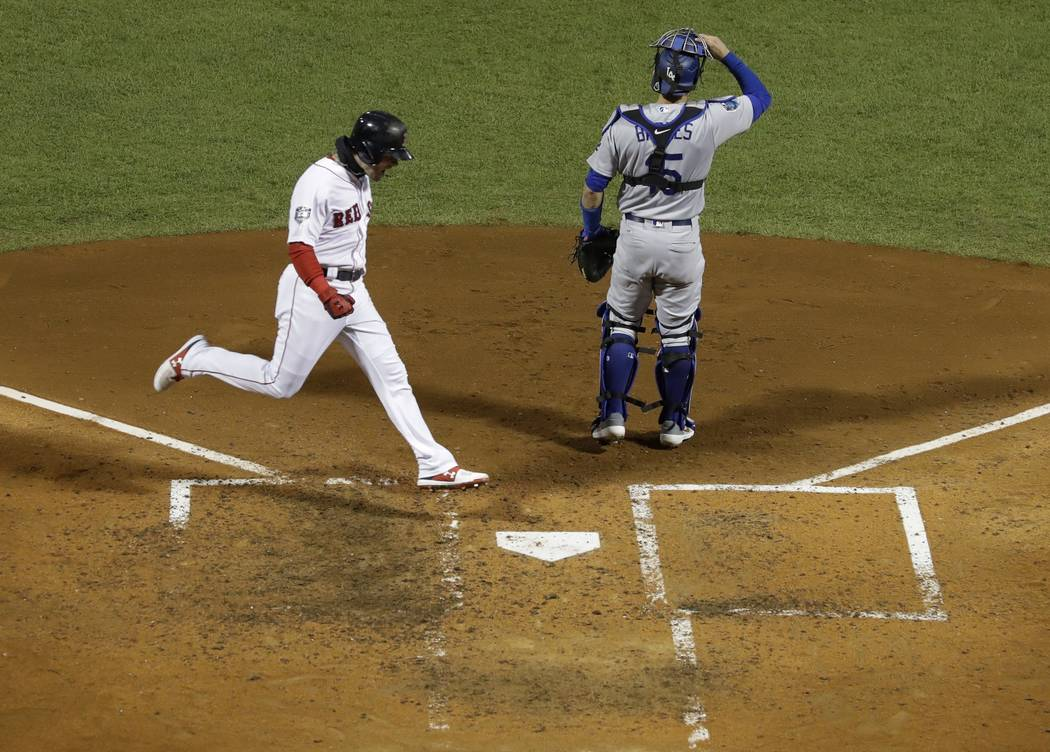 Boston Red Sox's Andrew Benintendi scores past Los Angeles Dodgers catcher Austin Barnes on a hit by J.D. Martinez during the fifth inning of Game 2 of the World Series baseball game Wednesday, Oc ...
