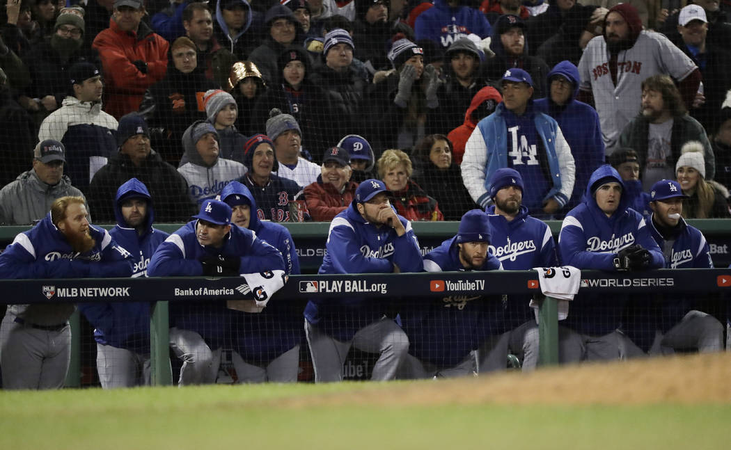 The Los Angeles Dodgers watch the ninth inning of Game 2 of the World Series baseball game from their dugout against the Boston Red Sox Wednesday, Oct. 24, 2018, in Boston. (AP Photo/David J. Phillip)
