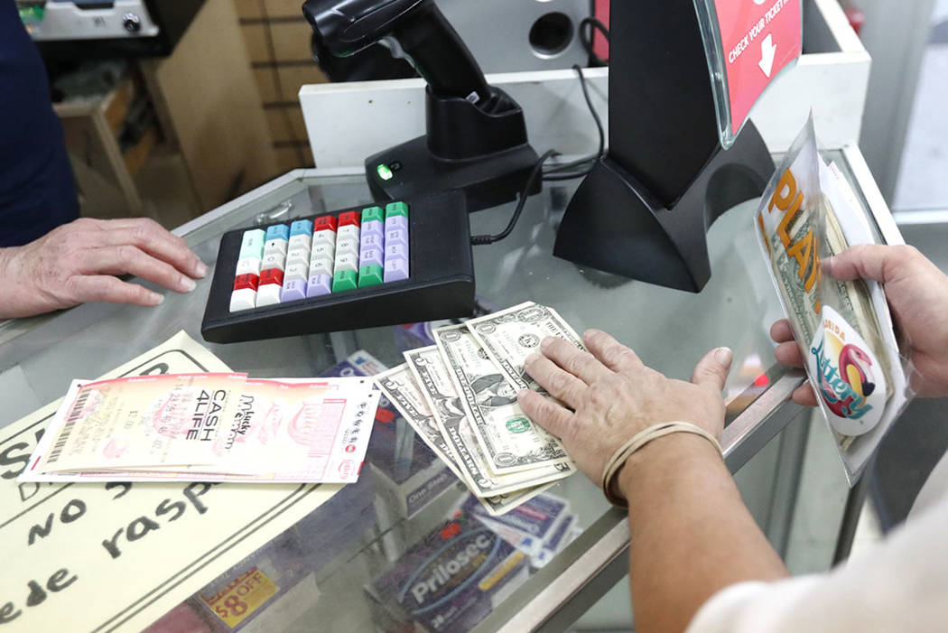 A customer purchases lottery tickets, Monday, Oct. 22, 2018, at La Preferida Superdiscount store in Hialeah, Fla. (AP Photo/Wilfredo Lee)
