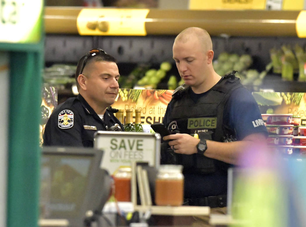 Members of the Louisville Metro Police Department talk inside a Kroger grocery in Jeffersontown, Ky., following a shooting that left two people dead, Wednesday, Oct. 24, 2018. (AP Photo/Timothy D. ...