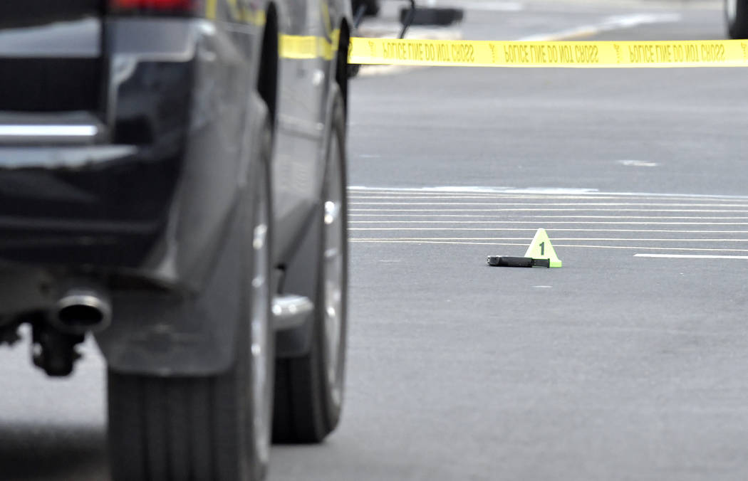 A gun lies on the ground next to an evidence marker outside of a Kroger Grocery in Jeffersontown, Ky., Wednesday, Oct. 24, 2018,. The shooting left two people dead, and the subject in custody. (AP ...