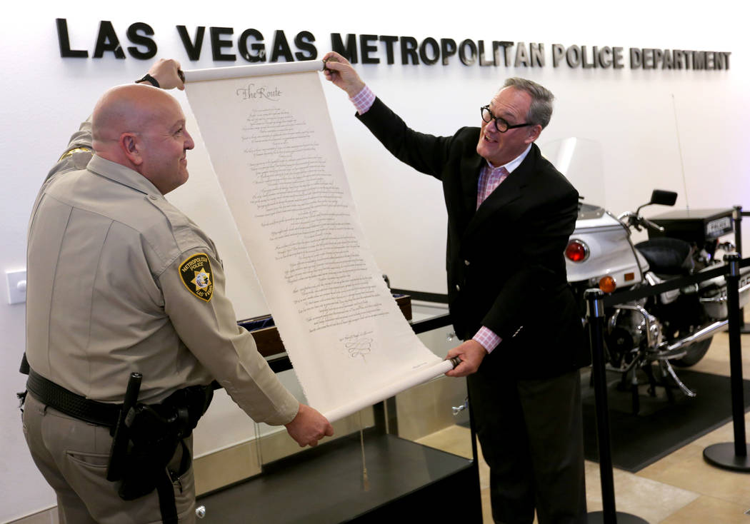 "Las Vegas police Lt. Harry Fagel and Nevada School of the Arts President and CEO Patrick Duffy unveil ""The Route"" poem scroll at Metropolitan Police Department headquarters in Las Vegas Thursday, ..."