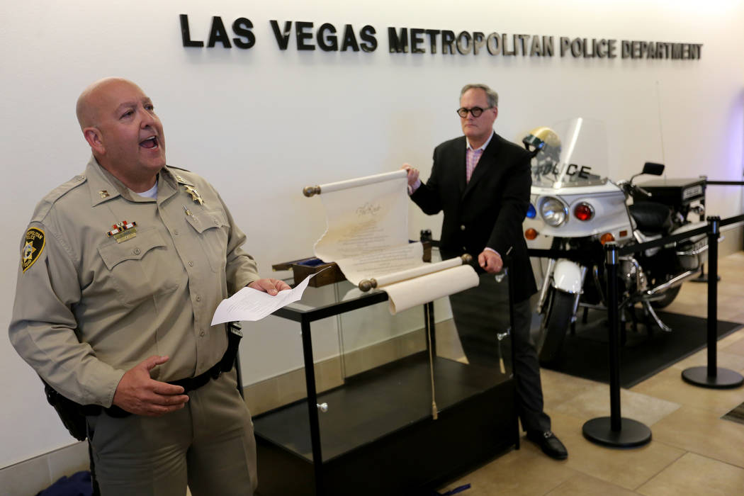 "Las Vegas police Lt. Harry Fagel recites his poem ""The Route"" on a scroll shown by Nevada School of the Arts President and CEO Patrick Duffy at Metropolitan Police Department headquarters in Las V ..."