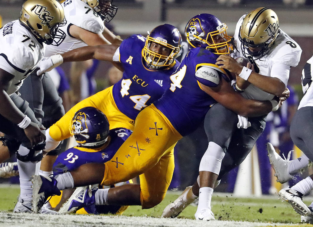 Central Florida's Darriel Mack Jr. (8) is tackled by East Carolina's Alex Turner (94) with Kendall Futrell (44) looking on during the first half of an NCAA college football game in Greenville, N.C ...