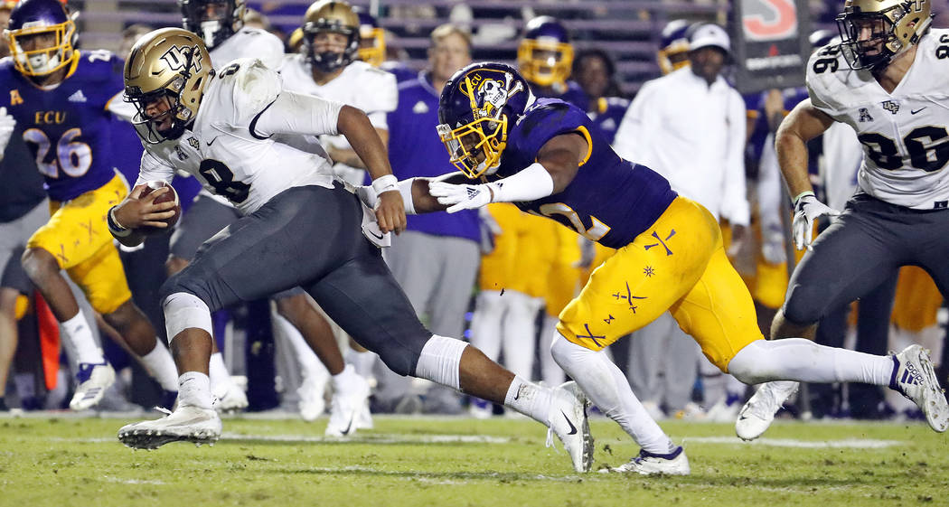 Central Florida quarterback Darriel Mack Jr. (8) tries to get away from East Carolina's Devon Sutton (42) during the first half of an NCAA college football game in Greenville, N.C., Saturday, Oct. ...