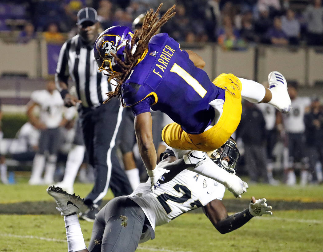 East Carolina's Deondre Farrier (1) collides with Central Florida's Richie Grant (27) during the second half of an NCAA college football game in Greenville, N.C., Saturday, Oct. 20, 2018. UCF won ...