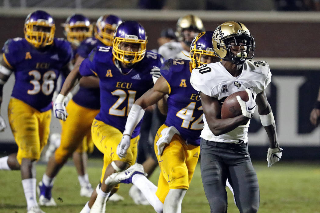 Central Florida's Greg McCrae (30) runs the ball for a touchdown with the East Carolina defense in pursuit during the second half of an NCAA college football game in Greenville, N.C., Saturday, Oc ...