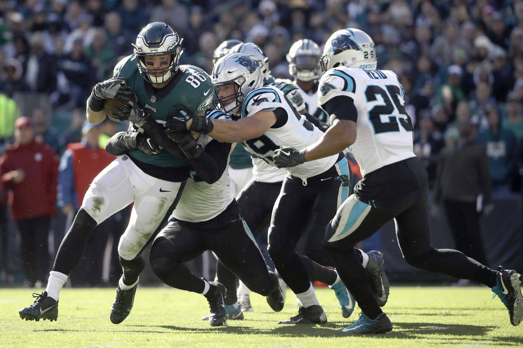 Philadelphia Eagles quarterback Carson Wentz (11) is tackled by a host of Carolina Panthers defenders during the second half of an NFL football game, Sunday, Oct. 21, 2018, in Philadelphia. (AP Ph ...