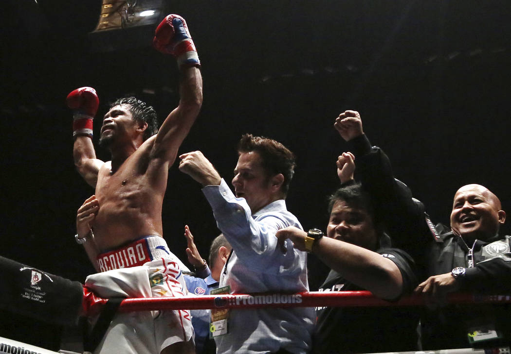 Manny Pacquiao of the Philippines, left, celebrates after defeating Lucas Matthysse of Argentina during their WBA World welterweight title bout in Kuala Lumpur, Malaysia, Sunday, July 15, 2018. Fi ...