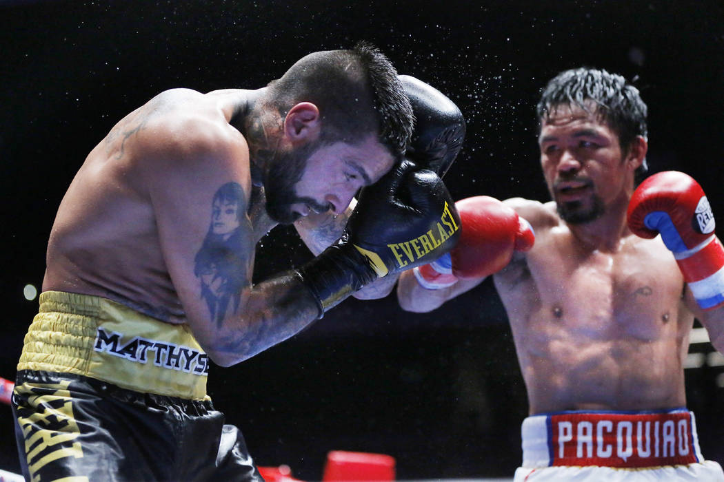 Lucas Matthysse of Argentina, left, shields himself from Manny Pacquiao of the Philippines, during their WBA World welterweight title bout in Kuala Lumpur, Malaysia, Sunday, July 15, 2018. Pacquia ...