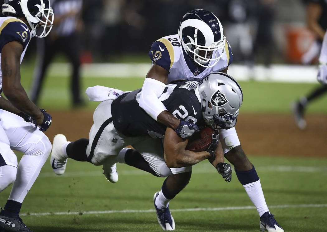 Oakland Raiders running back Doug Martin is brought down with the ball by Los Angeles Rams defensive back Lamarcus Joyner (20) during the first half of an NFL football game in Oakland, Calif., Mon ...