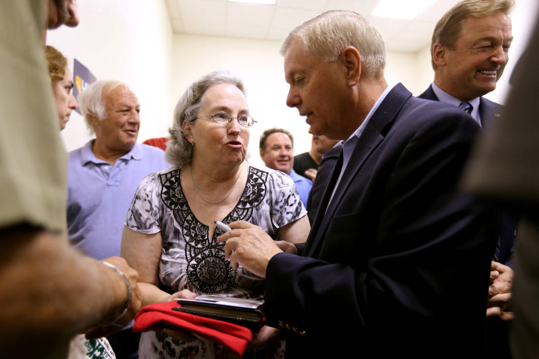 Robyn Collier of Las Vegas gets an autograph from U.S. Sen. Lindsey Graham, R-S.C., during a campaign event for U.S. Sen. Dean Heller, R-Nev., right, and 3rd Congressional District candidate Danny ...