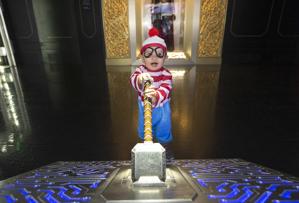 """Las Vegas resident Angelo Barrett, 1, dressed in a """" Where's Waldo? """" costume pulls on Thor's Hammer at the Mjolnir Simulation during a Trick-or-Treat event at the Marvel Avengers S.T.A.T.I.O.N. i ..."""