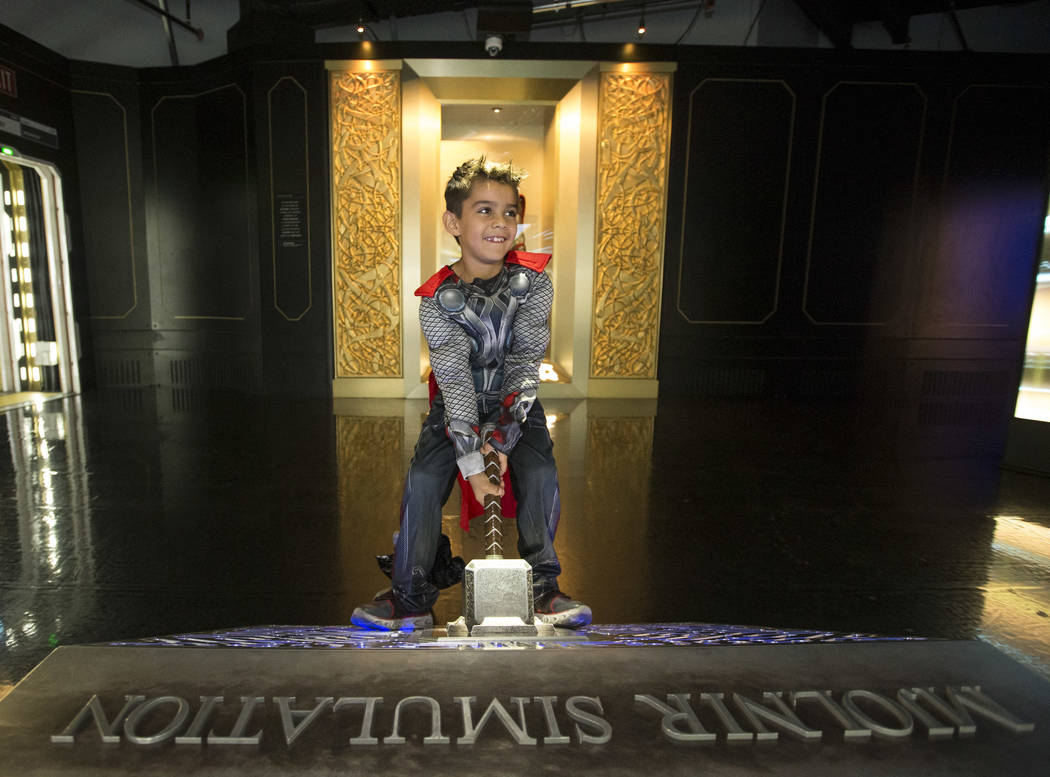 Las Vegas resident Asher Barrett, 7, dressed as Thor pulls on Thor's hammer at the Mjolnir Simulation in the Thor exhibition room during a Trick-or-Treat event at the Marvel Avengers S.T.A.T.I.O.N ...