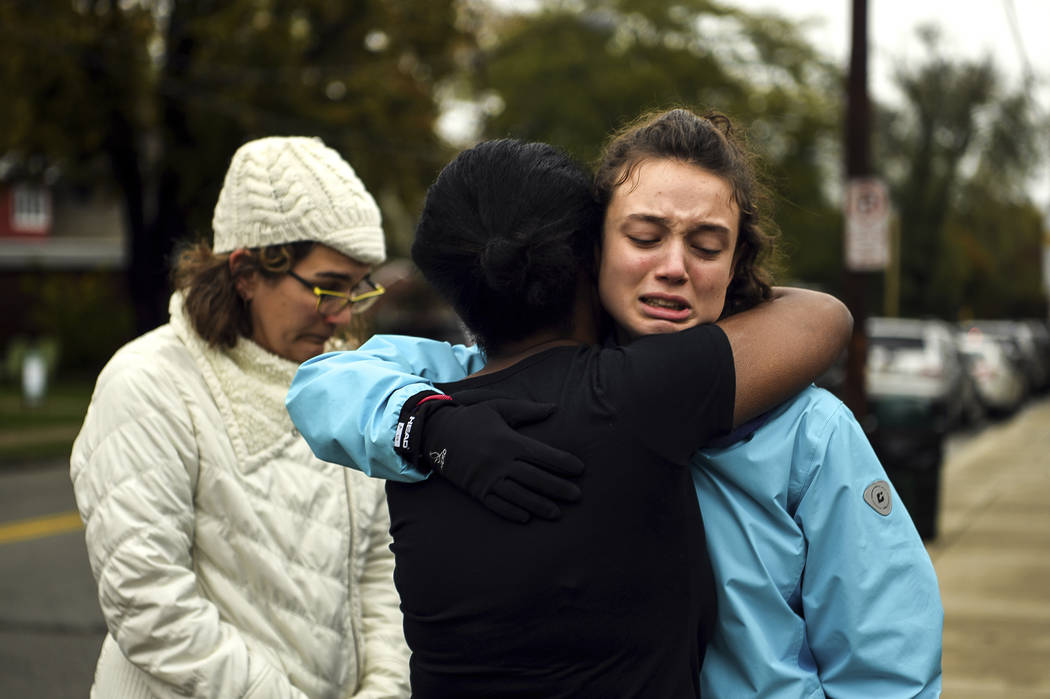 From left, Kate Rothstein looks on as Tammy Hepps hugs Simone Rothstein, 16, on the intersection of Shady Avenue and Northumberland Street after multiple people were shot at The Tree of Life Congr ...